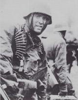 Nieznany z imienia celowniczy MG42, za pazuchą nóż okopowy, na sobie ma prawdopodobnie amerykańskie poncho przeciwdeszczowe.